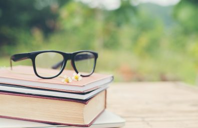 Book and eye glasses for read and write over blurred nature outdoor background.